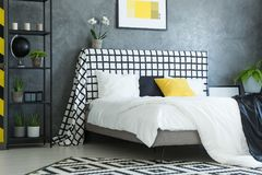 Scandinavian bedroom with white orchid. Yellow black and white pillow on king-size bed with white orchid on checkered bedhead in scandinavian bedroom Royalty Free Stock Photo