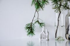 Scandinavian Christmas decor. pine branches and a ceramic house stock photo