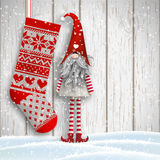 Scandinavian christmas traditional gnome, Tomte, with knitted stocking, illustration. Scandinavian christmas motive, Tomte standing in front of gray wooden wall Royalty Free Stock Photos