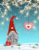 Scandinavian christmas traditional gnome, Tomte standing uder branches decorated with electric lights and hanging red. Heart, Nisser in Norway and Denmark Stock Photos