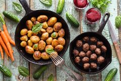 Scandinavian cuisine. Fried potatoes, meatballs and lingonberry. Drink served with vegetables and herbs on rustic blue table overhead view stock photography