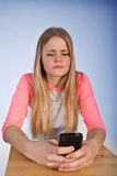 Scandinavian cute young girl looking irritated at her phone Royalty Free Stock Photo
