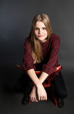 Scandinavian cute young girl sitting on a chair Royalty Free Stock Photo