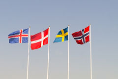 Scandinavian Flags on a blue heaven. National flags of Iceland, Denmark, Sweden and Norway Royalty Free Stock Images
