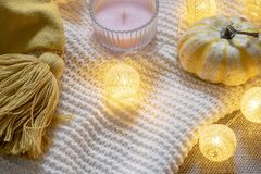 Scandinavian inspired winter flat lay - tassel cushion, candle, pumpkin and garland on white knitted plaid, hygge style. Copy space royalty free stock image