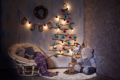 Scandinavian interior design of Cgristmas room. Scandinavian interior design of room in winter holiday time. Decorated Cristmas tree made of wooden branches. New Stock Photo