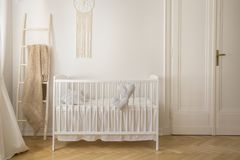 Scandinavian nursery with white wooden crib, real photo with copy space stock photos