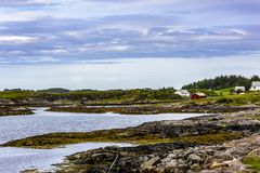 Scandinavian Ocean Bliss. A calming Ocean Vista with a gorgeous cloudscape and rocky island formations in the background and tide pools in the foreground Stock Images