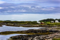 Scandinavian Ocean Bliss. A calming Ocean Vista with a gorgeous cloudscape and rocky island formations in the background and tide pools in the foreground Royalty Free Stock Image
