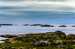 Scandinavian Ocean Bliss. A calming Ocean Vista with a gorgeous cloudscape and rocky island formations in the background and tide pools in the foreground Stock Photo