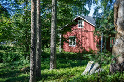 Scandinavian old red wooden house in forest Stock Photo