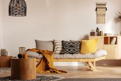 Scandinavian sofa with pillows and dark yellow blanket in bright living room interior with black chandelier stock photos