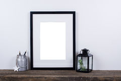 Scandinavian style empty photo frame mock up. Minimal home decor. Scandinavian style empty photo poster frame mock up. Minimal home decor on rustic wooden board royalty free stock photography