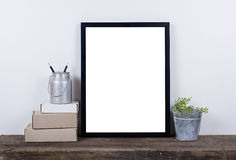 Scandinavian style empty photo frame mock up. Minimal home decor. Scandinavian style empty photo poster frame mock up. Minimal home decor on rustic wooden board stock images