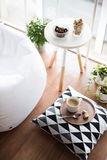 Scandinavian style hipster interior, cozy loft room. Coffee served on table in bright light scandinavian style hipster interior, cozy loft room with large Stock Photos