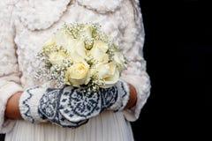 Scandinavian style wedding. Bride holding wedding white rose bouquet wearing mittens Royalty Free Stock Photos