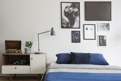 Scandinavian style, wooden dresser by a navy blue bed and framed art gallery on a white wall of a creative bedroom stock images