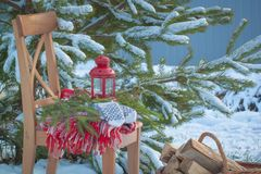 Scandinavian style wool mittens on Christmas plaid and chair near basketful of firewood Royalty Free Stock Images
