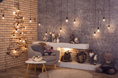 Scandinavian winter interior of room. Horizontal. Creative wooden Christmas tree at the brick wall of Loft style room with burning bulbs garland and modern Stock Photography