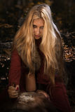 Scandinavian witch pythoness with runes. On a forest background Stock Images