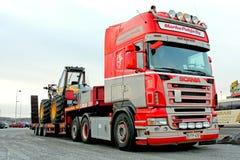Φορτηγό Scania που μεταφέρει μια δασική θεριστική μηχανή Στοκ εικόνα με δικαίωμα ελεύθερης χρήσης