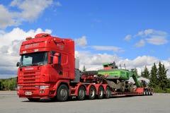 Φορτηγό Scania 164G 480 που μεταφέρει τη μηχανή υλικού χειρισμού Στοκ εικόνες με δικαίωμα ελεύθερης χρήσης