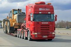 Scania 164G transporta el cargador pesado de la rueda de Volvo Foto de archivo