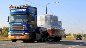 Scania R500 acarrea la carga ancha acompañada por un acompañamiento Car Imagen de archivo libre de regalías