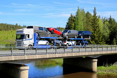 Scania R480 Auto Carrier Hauls New Cars on Bridge. FORSSA, FINLAND - MAY 30, 2015: White Scania R480 auto carrier hauls a load of new cars along bridge. The Stock Image