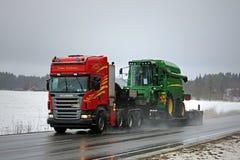 Scania R560 semi транспортирует зернокомбайн John Deere вдоль шоссе Стоковые Изображения