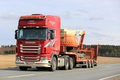 Scania rouge transporte semi l'ascenseur de boom le long de la route Photos libres de droits