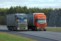 Scania Semi Truck Overtakes another Truck. PAIMIO, FINLAND - OCTOBER 16, 2015: Scania 124L Semi overtakes another truck on motorway. Trucks with heavy cargo can Royalty Free Stock Images