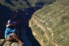 Scanning the goosenecks. Woman with purple cowboy hat sitting on the edge of deep canyon looking through binoculars at landscape Stock Photography