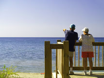 Scanning the Horizon. An older couple stand at a railing overlooking a wide expanse of lake or ocean water royalty free stock images