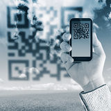 Scanning Qr code with mobile smart phone. On sky background Stock Images