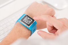 Scanning quick response code with smart watch. Man is scanning quick response code with blue smart watch Stock Photos