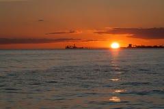 Scape del cielo e petroliere al tramonto Immagine Stock