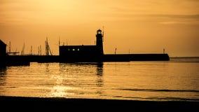 Scarborough harbour lighthouse pier. Lighthouse pier harbour sunset reflection Stock Photos