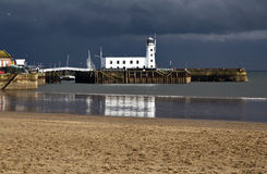 Scarborough Light House, it's white walls silhouetted by dark storm clouds. Scarborough, North Yorkshire. The Lighthouse dominates the scenery and views of the Royalty Free Stock Photo