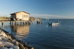 SCARDOVARI, ITÁLIA, 2016-08-06: Cabanas da pesca na lagoa de Scardovari Imagens de Stock