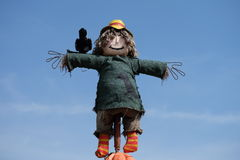 Scarecrow in blue sky with a bird on shoulder Stock Photo