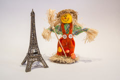 Scarecrow and eifel tower. A funny colorful scarecrow with the eifel tower Royalty Free Stock Photography