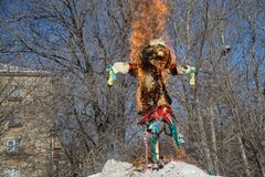 Scarecrow in the fire for the Slavic holiday Maslenitsa. Folk traditions stock images