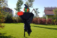 Scarecrow in the form of an evil witch with a pumpkin Royalty Free Stock Photo