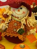 Scarecrow girl surrounded by seasonal decor. Smiling face, corn stalks hair braids, jaunty hat and daisy print dress on a doll-size scarecrow surrounded by Royalty Free Stock Images