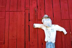 Scarecrow hanging against a vibrant red barn Royalty Free Stock Photos
