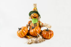 Scarecrow with pumkins. A scarecrow sits with his pumpkins against a white background Royalty Free Stock Photo