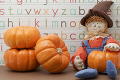 Scarecrow sitting against Alphabet background holding pumpkin Stock Images