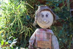Scarecrow sitting in the autumn garden stock photography