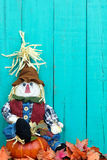 Scarecrow sitting on pumpkin by fall leaves Stock Photography